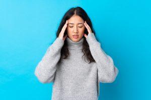 Donna con mal di testa su sfondo azzurro