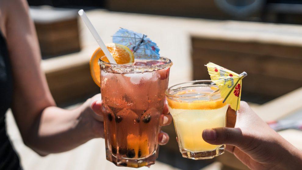 Dettaglio di due persone che fanno cin cin con due bicchieri di cocktail ghiacciati