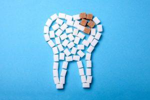 Tante zollette di zucchero bianco poste in modo da formare un dente. Alcune zollette di zucchero marrone simboleggiano la carie.