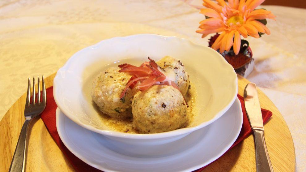 Un piatto con all'interno tre canederli e, accanto, un fiore