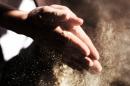 Un uomo unisce le mani sporche di farine