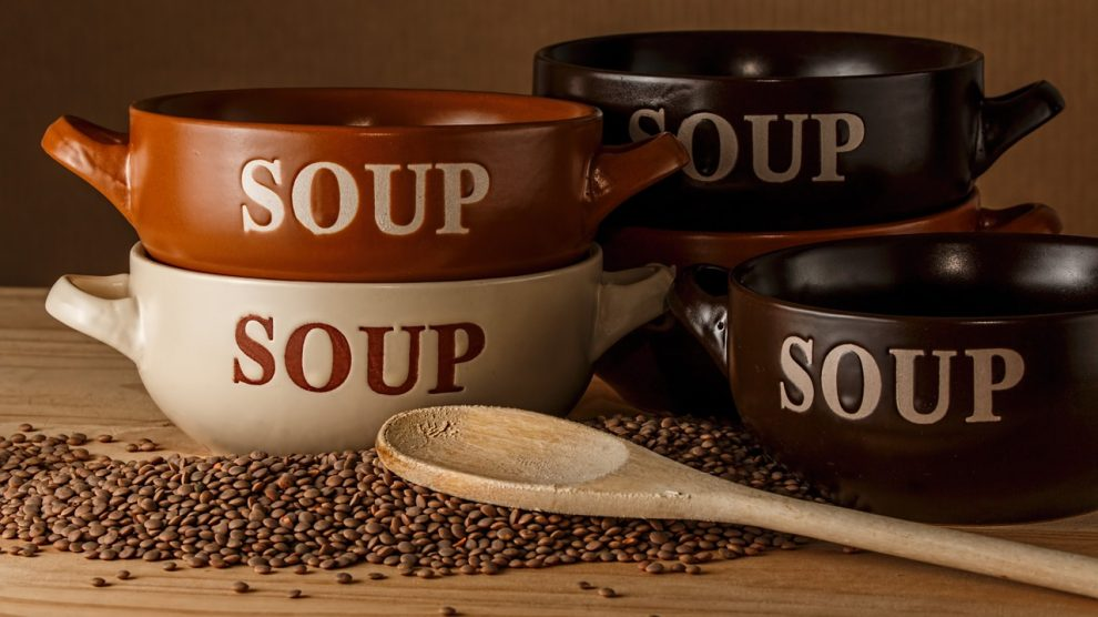 Quattro pentolini da zuppa su un tavolo di legno