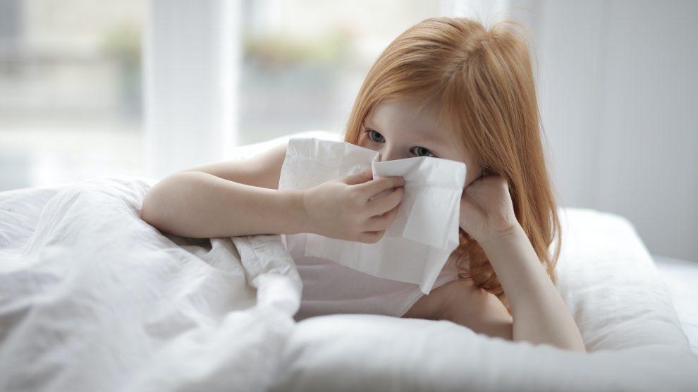 una bambina è sotto le coperte e si soffia il naso
