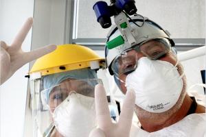 Un dentista e la sua assistente salutano in camera facendo il gesto della vittoria, completamente bardati con i dispositivi di protezione individuali richiesti dalle misure di prevenzione contro la diffusione del covid19