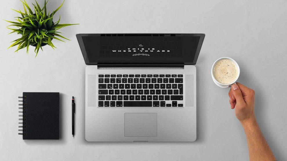 su una scrivania ci sono una agenda, una piantina, un computer portatile e una tazza di caffè