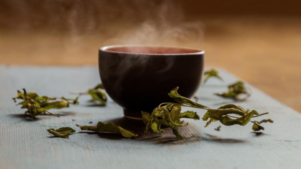Una tazza di tè, circondata da foglie di menta