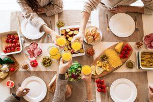una tavolata imbandita di cibo (pomodori, olive, formaggi, pane, grissini e insalata) inquadrata dall'alto. Al tavolo quattro persone che stanno facendo un brindisi con un succo di frutta