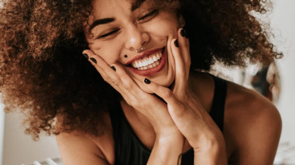 Una ragazza riccia con piercing al naso e al labbro sorride, tenendo il viso tra le mani