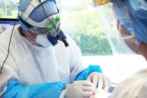 Il dottor Maurizio Pedone al lavoro mentre opera un paziente assistito da una ASO (assistente di studio odontoiatrico)