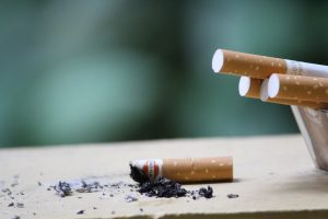 Una sigaretta consumata e spenta, accanto a un posacenere pieno di sigarette