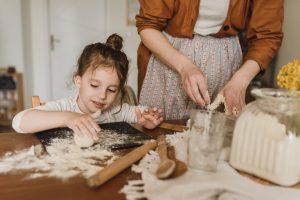 Una bimba e una mamma preparano taralli
