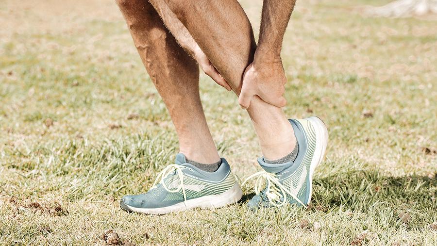Un uomo sportivo, inquadrato dal ginocchio in giù, si tiene con entrambi le mani la caviglia sinistra