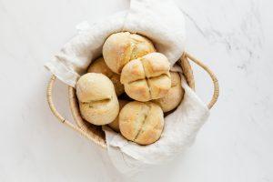 Un cestino di vimini contenente pane bianco, poggiato su una lastra di marmo bianco