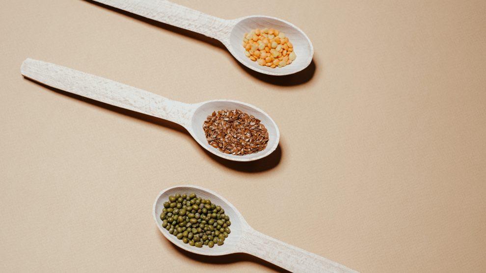 Tre mestoli di legno che contengono legumi, tra cui piselli e lenticchie