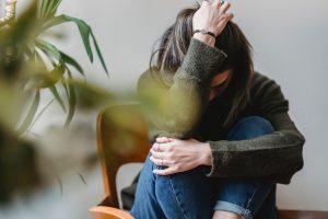 Una ragazza è accovacciata su una sedia in legno, si tiene con un braccio le ginocchia e con l'altro la testa.