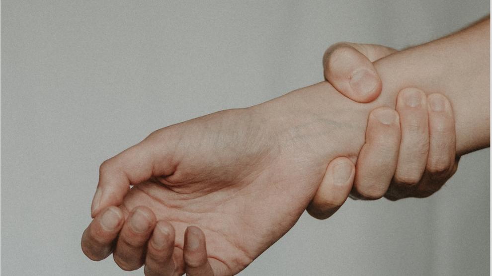 Dettaglio fotografico di una persona che si tiene il polso dolorante con l'altra mano