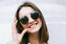 Una ragazza sorride mentre indossa un paio di occhiali da sole scuri con lenti tonde e molto grandi