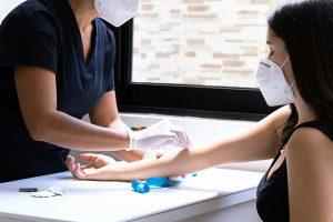 Un'inferiera effettua un prelievo del sangue a una paziente. Entrambe indossano la mascherina ffp2